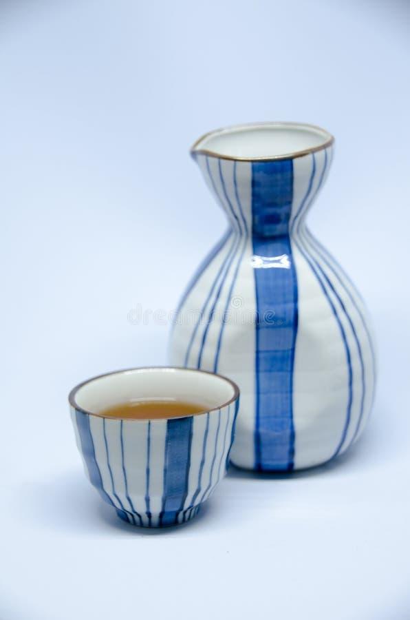 Бутылка и чашка ради на яркой белой предпосылке стоковое фото