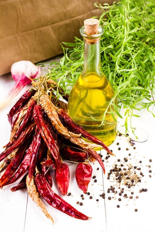 Бутылка оливкового масла, травы, чеснок и накаленный докрасна перец chili на whit стоковые изображения rf