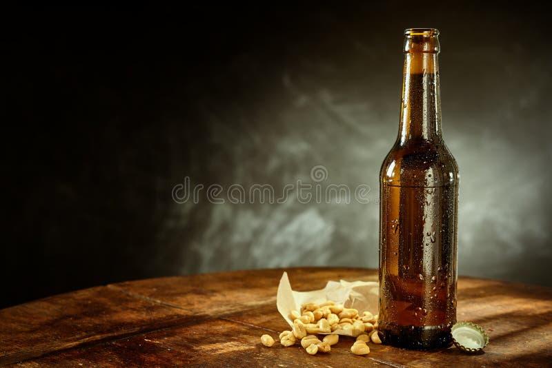 Бутылка пива на таблице с арахисами и крышкой стоковые изображения rf