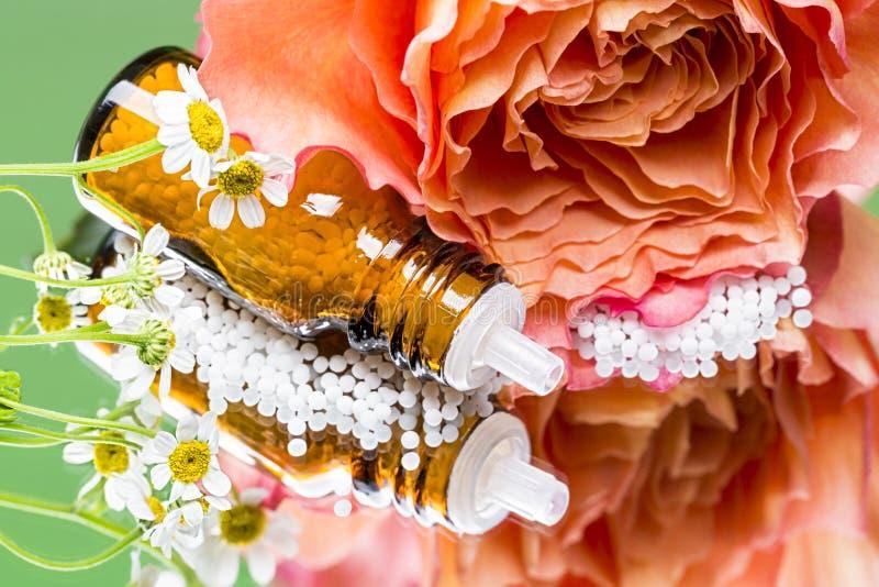 Бутылка при глобулы гомеопатии кладя на зеркало стоковые фото