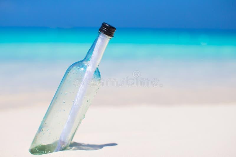 Бутылка при сообщение похороненное в белом песке стоковые фотографии rf