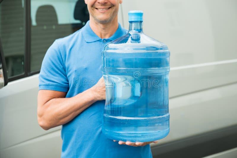 Бутылка с водой нося работника доставляющего покупки на дом стоковая фотография rf