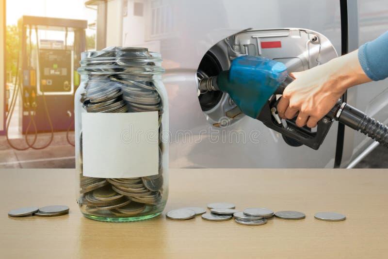 Бутылка с монетками, рука денег держа лить форсунки горючего стоковая фотография