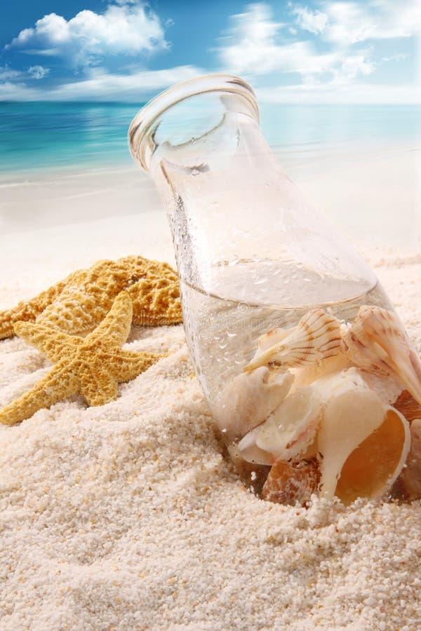 Бутылка с раковинами в песке стоковые фотографии rf