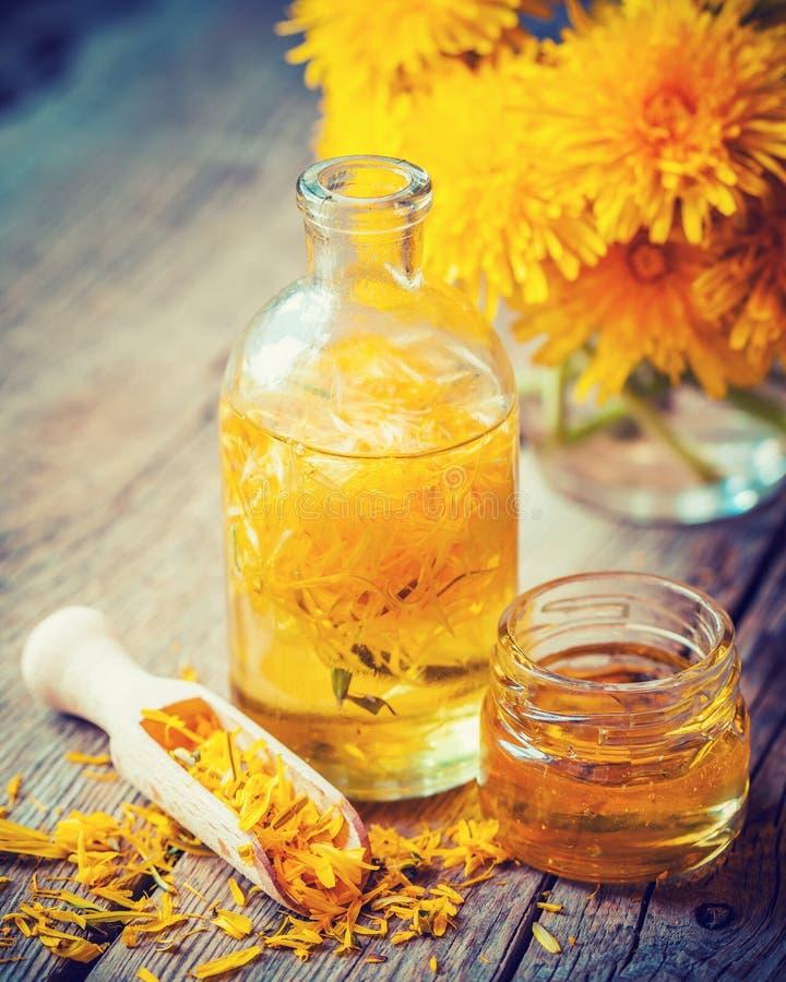 Бутылка тинктуры или масла одуванчика, пук цветка и мед раздражают стоковое изображение