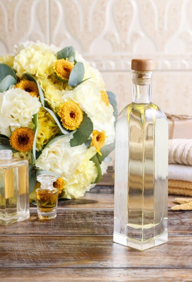 Бутылка эфирного масла, букета желтой гвоздики цветет стоковая фотография