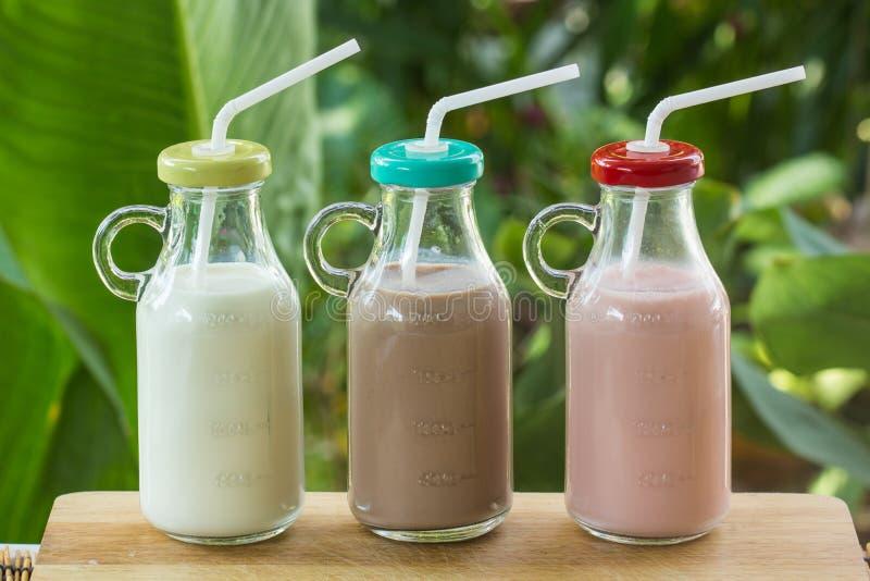 Бутылки клубники, шоколада и парного молока стоковые изображения rf