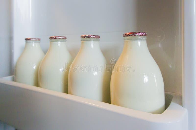 Бутылки молока в двери холодильника стоковое фото rf