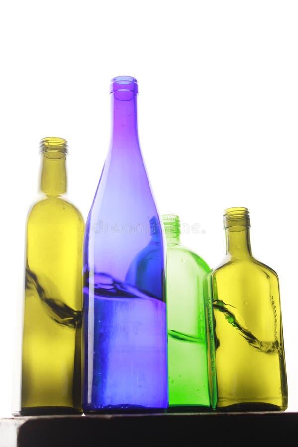 Бутылки покрашенные стеклом на белой предпосылке стоковая фотография rf