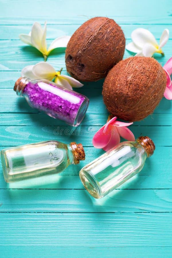Бутылки с кокосовым маслом, кокосами и солью моря на ярком wo стоковое фото rf