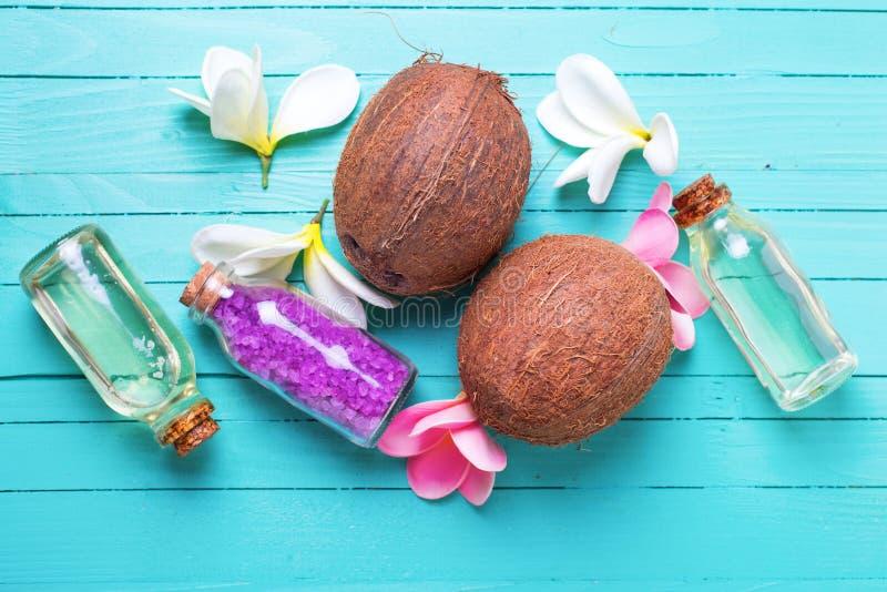 Бутылки с кокосовым маслом, кокосами и солью моря на ярком wo стоковые фото