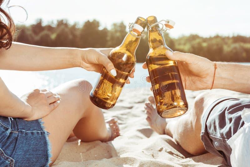 Бутылки человека и женщины clinking пива пока отдыхающ на пляже стоковое изображение rf