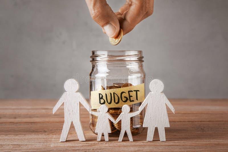 буферов Стеклянный опарник с монетками и надписью бюджет и символ семьи с детьми Человек держит монетку в руке стоковая фотография rf