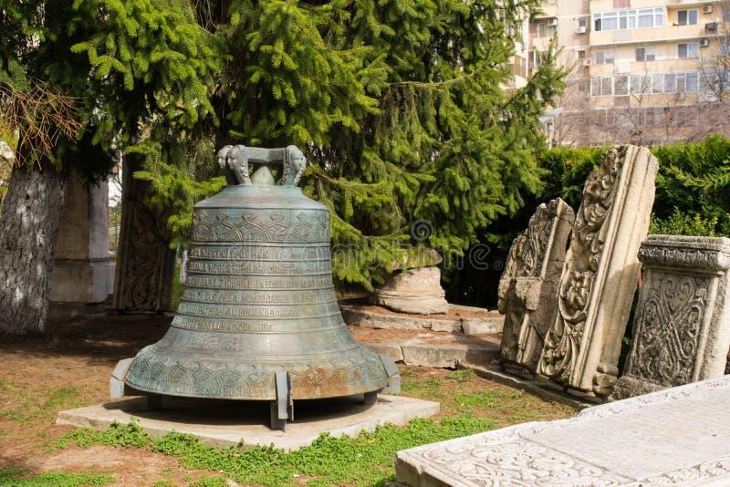 Бухарест, Румыния - 16-ое марта 2019: большой бронзовый церковный колокол расположенный во двор  церков стоковые изображения