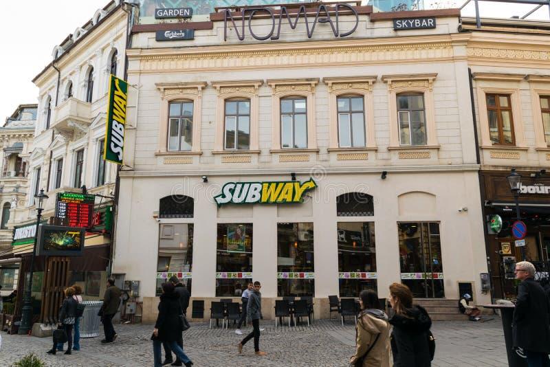 Бухарест, Румыния - 16-ое марта 2019: Туристы идя на метро ресторан на улице Lipscani в старой части городка Бухареста, стоковое изображение