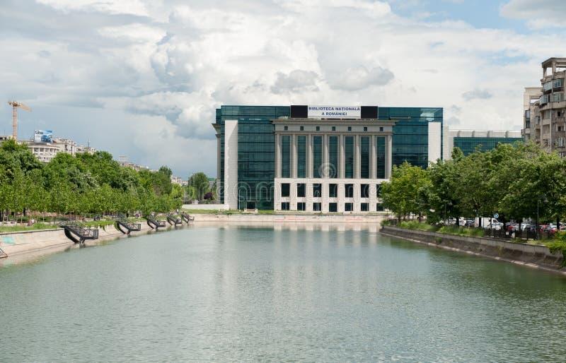 БУХАРЕСТ, РУМЫНИЯ - 14-ОЕ МАЯ 2017: Река в городе Бухареста, Румынии Городской пейзаж Национальная библиотека в предпосылке стоковые изображения rf