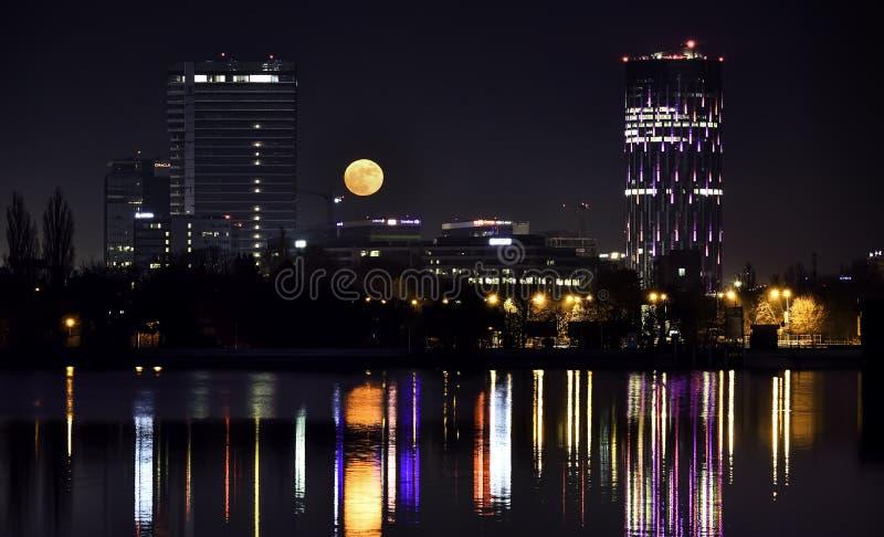 БУХАРЕСТ SKYTOWER Румыния к ноча от озера Herastrau стоковые изображения rf