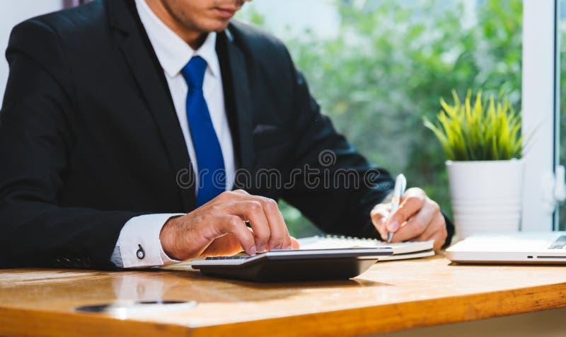 Бухгалтерия бизнесмена используя высчитывать и работу с компьтер-книжкой c стоковое фото