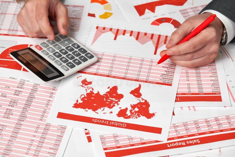 Бухгалтер бизнесмена используя калькулятор для высчитывать финансы на офисе стола Отчеты о концепции финансового учета дела красн стоковые фотографии rf