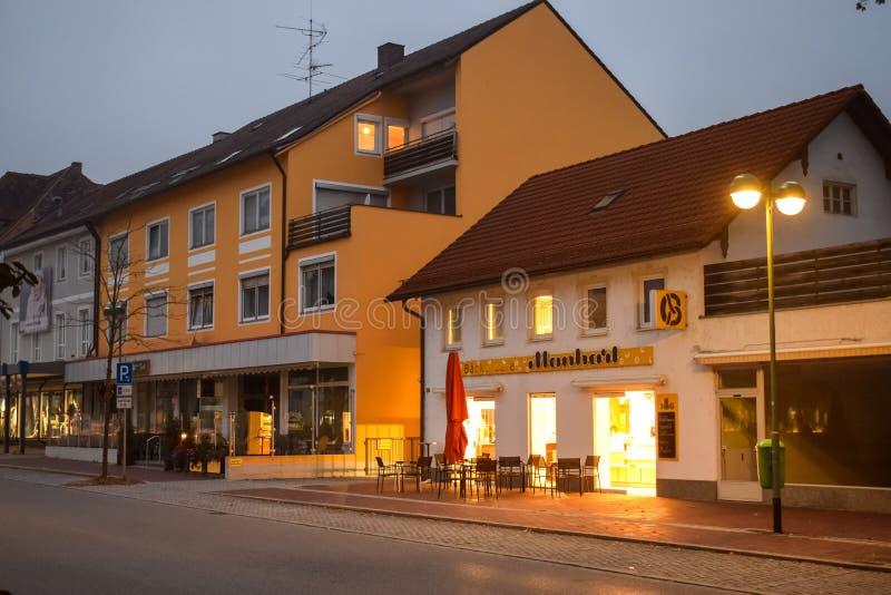 БУХЛО, ГЕРМАНИЯ - ОКТЯБРЬ 09, 2018: Свет из кафе на пустой улице утром в Бучло-Германия стоковые фотографии rf