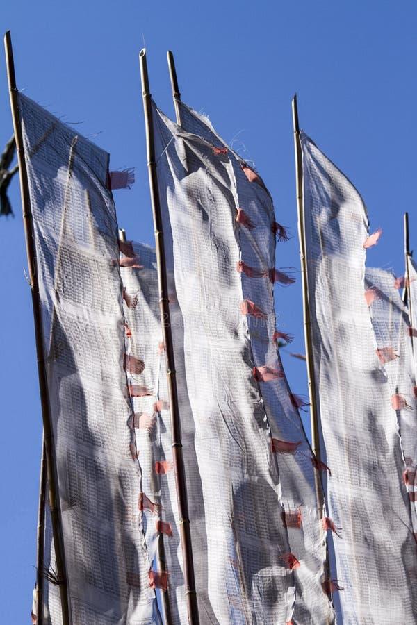 Буддийская молитва сигнализирует на ветре против голубого неба стоковая фотография