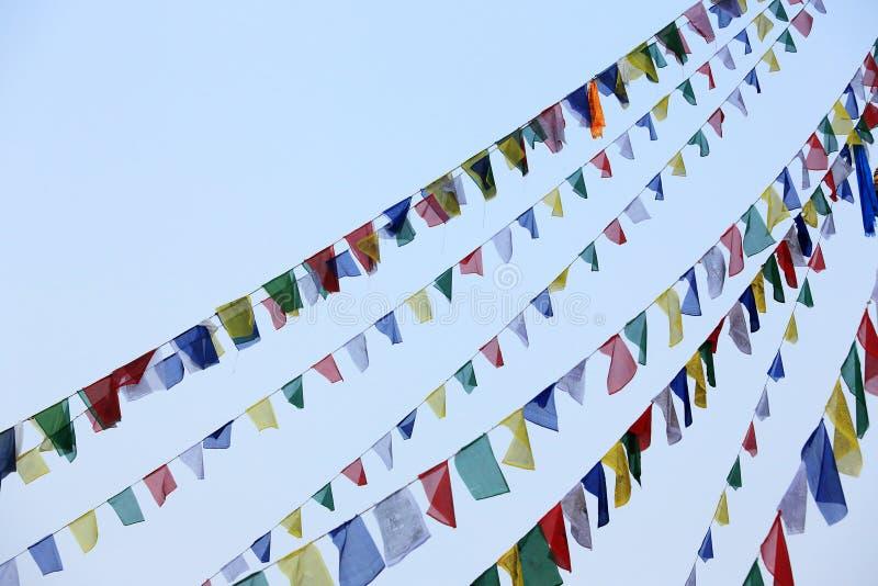 Буддийская тибетская молитва сигнализирует развевать в ветре против голубого sk стоковые фотографии rf