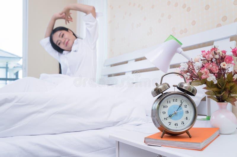 Будильник крупного плана имеет славный день с счастливой женщиной в кровати после просыпать вверх после просыпать вверх стоковые фото