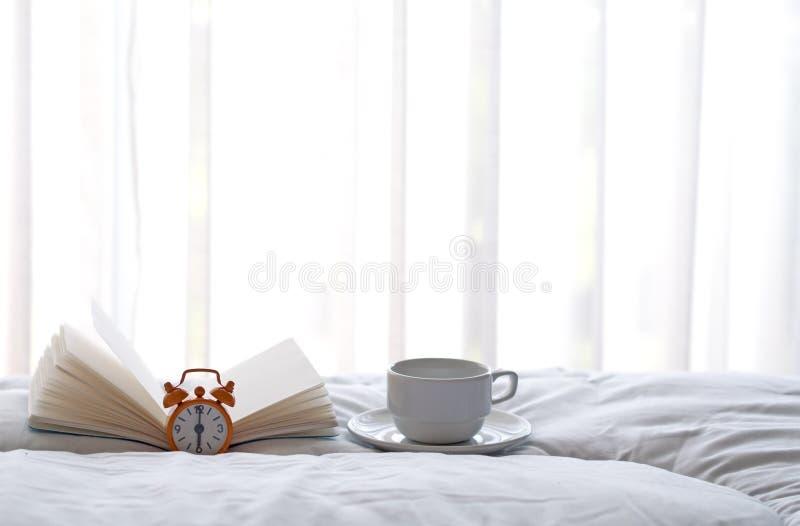 Будильник на кровати с кофе и книгой в утре стоковое изображение rf