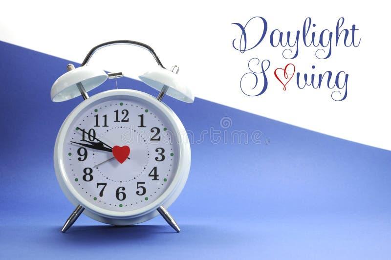 Будильник ретро винтажного стиля белый на голубой и белой предпосылке с текстом образца сбережений дневного света стоковое фото