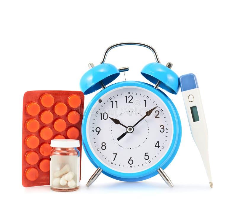 Будильник рядом с таблетками и термометром стоковые изображения
