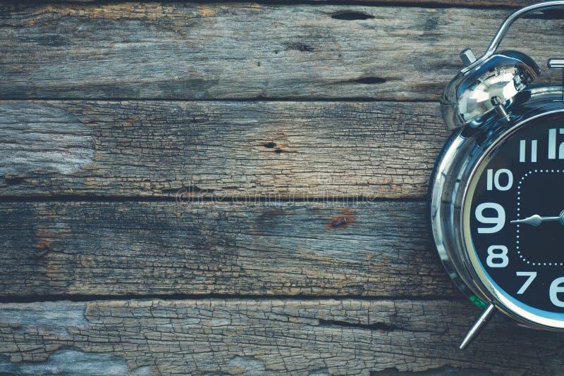 Будильник сияющего металла классический на очень старом backgro деревянного стола стоковое фото rf