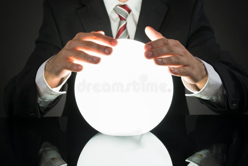Будущее бизнесмена предсказывая с хрустальным шаром стоковое изображение rf