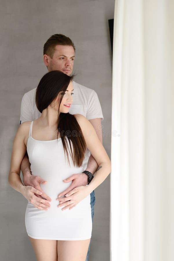 Будущий папа стоя за его красивой беременной женой стоковые изображения rf
