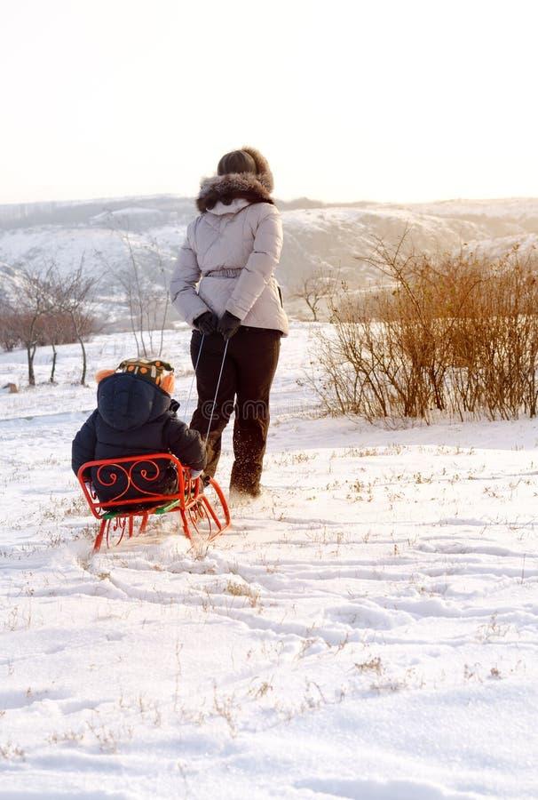 Будьте матерью вытягивать toboggan с ее ребенком в снеге стоковые фотографии rf