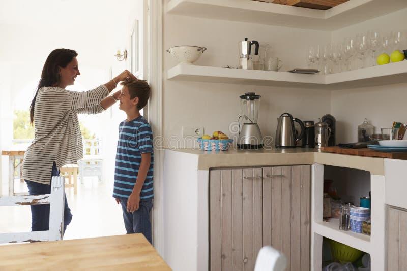 Будьте матерью измеряя высоты ` s сына против стены стоковые изображения