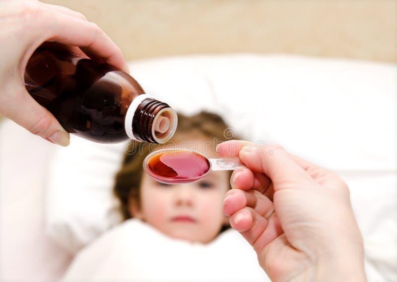 Будьте матерью лить лекарства в ложке на переднем плане и больном стоковые фото