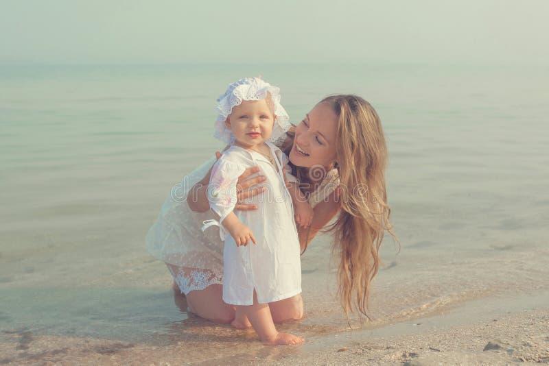 Будьте матерью и ее дочь имея потеху на пляже стоковые фото