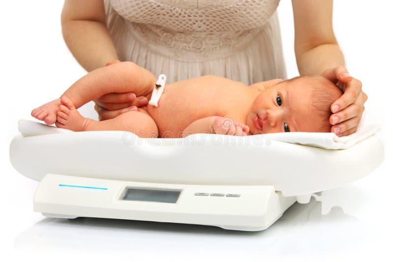 Будьте матерью и ее newborn младенец на масштабе веса стоковое фото rf