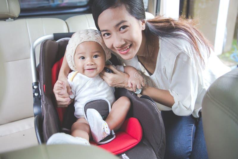 Будьте матерью обеспечивать ее младенца в автокресле в ее автомобиле стоковое фото rf