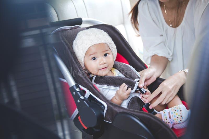 Будьте матерью обеспечивать ее младенца в автокресле в ее автомобиле стоковое изображение