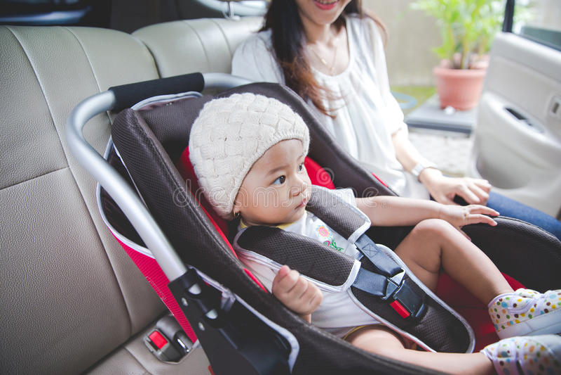 Будьте матерью обеспечивать ее младенца в автокресле в ее автомобиле стоковая фотография