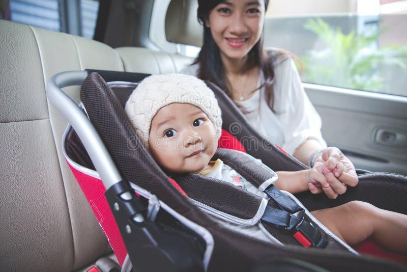 Будьте матерью обеспечивать ее младенца в автокресле в ее автомобиле стоковое изображение rf