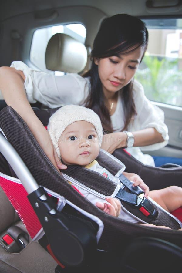 Будьте матерью обеспечивать ее младенца в автокресле в ее автомобиле стоковое фото