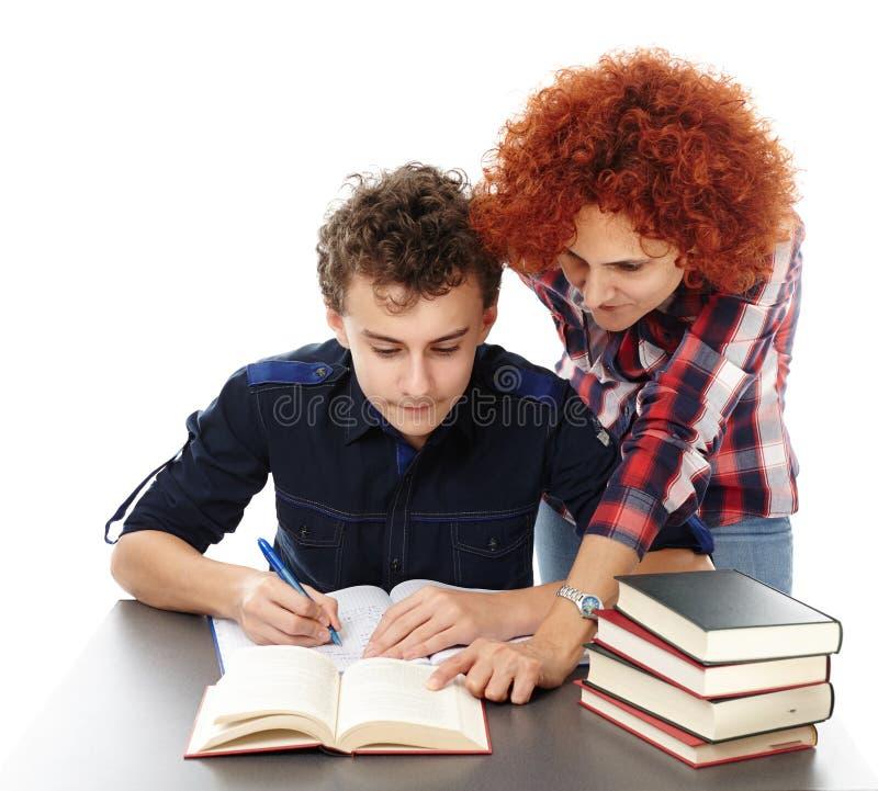 Будьте матерью стола стоящего близко сына помогая ему делая его домашнюю работу стоковое изображение rf