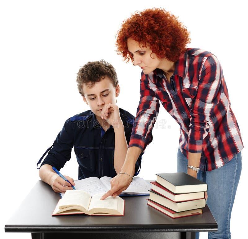 Будьте матерью стола стоящего близко сына помогая ему делая его домашнюю работу стоковая фотография