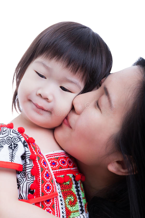 Будьте матерью целовать ее прелестную маленькую щеку дочери, на белизне стоковое фото