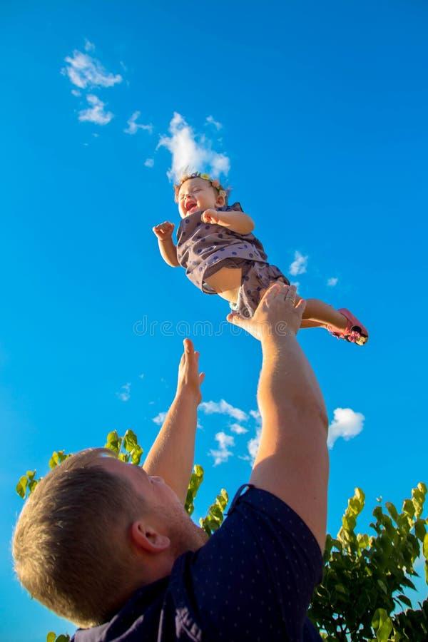 Будьте отцом бросает вверх и улавливает младенца стоковое изображение