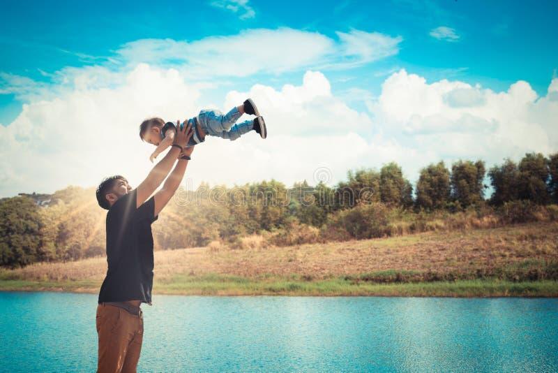 Будьте отцом бросать его сына на парк реки Концепция дружелюбного f стоковые фотографии rf