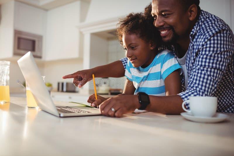 Будьте отцом использующ компьтер-книжку пока помогающ его дочери с домашней работой стоковые фотографии rf