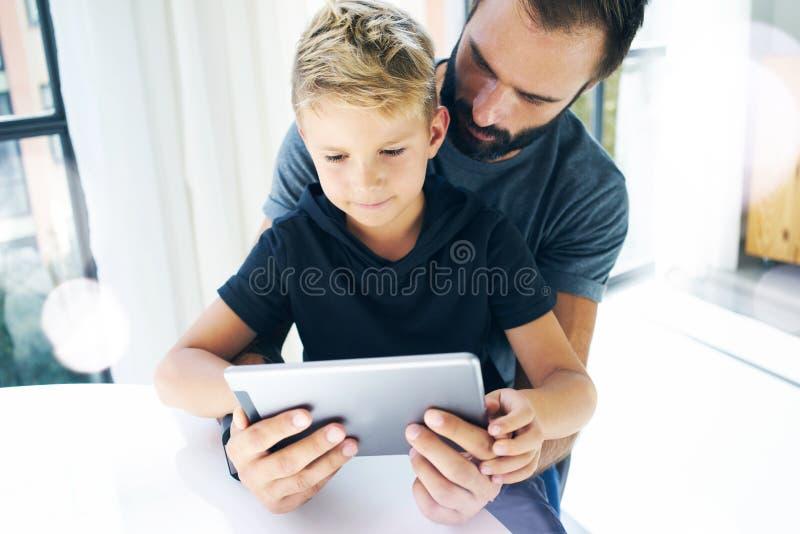Будьте отцом и его маленький сын играя совместно на мобильном компьютере, отдыхать крытый Бородатый человек при молодой мальчик и стоковые фото
